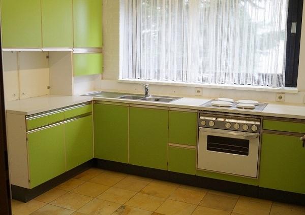 Белые прозрачные занавески, белые стены и столешница на зеленой кухне
